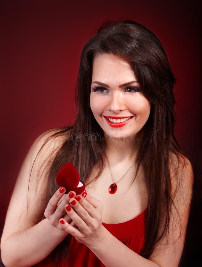 Ragazza con il contenitore di monili su priorità bassa rossa. immagine stock libera da diritti