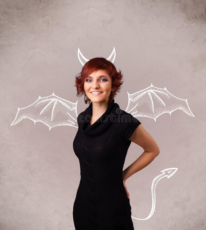 Ragazza con il disegno dei corni e delle ali del diavolo immagine stock