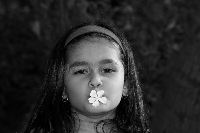 Ragazza con il fiore in bocca fotografie stock libere da diritti