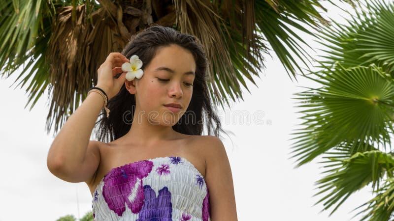 Ragazza con il fiore in capelli che stanno sotto la palma immagini stock libere da diritti