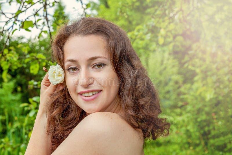 Ragazza con il fiore della rosa di bianco in sua mano in parco fotografia stock libera da diritti