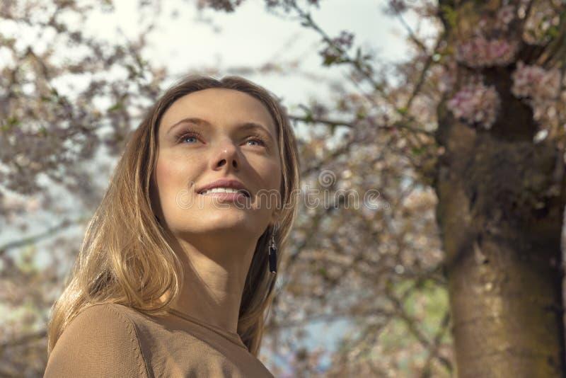 Ragazza con il fiore di ciliegia Bella giovane donna bionda fotografia stock libera da diritti