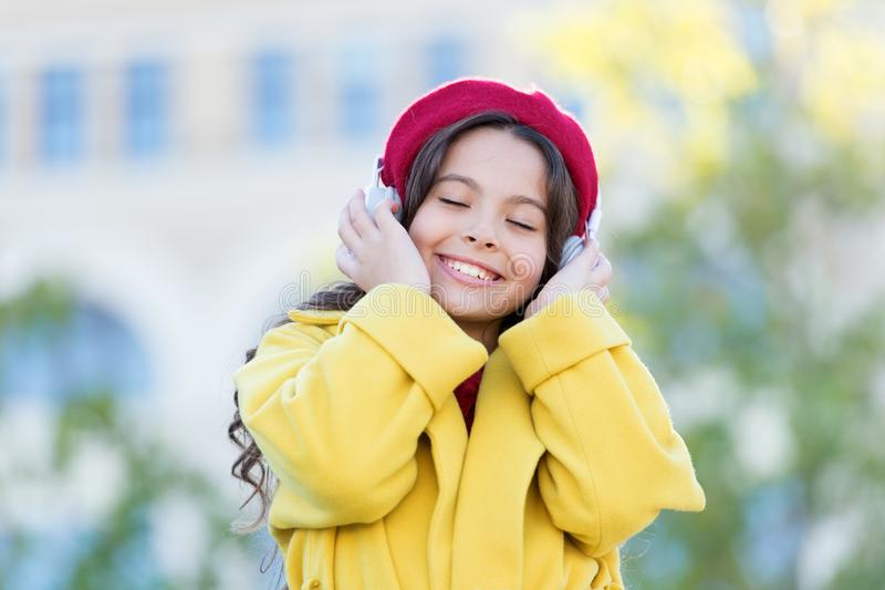 Ragazza con il fondo urbano delle cuffie Influenza positiva di musica Attrezzatura francese di stile della ragazza del bambino ch immagine stock libera da diritti