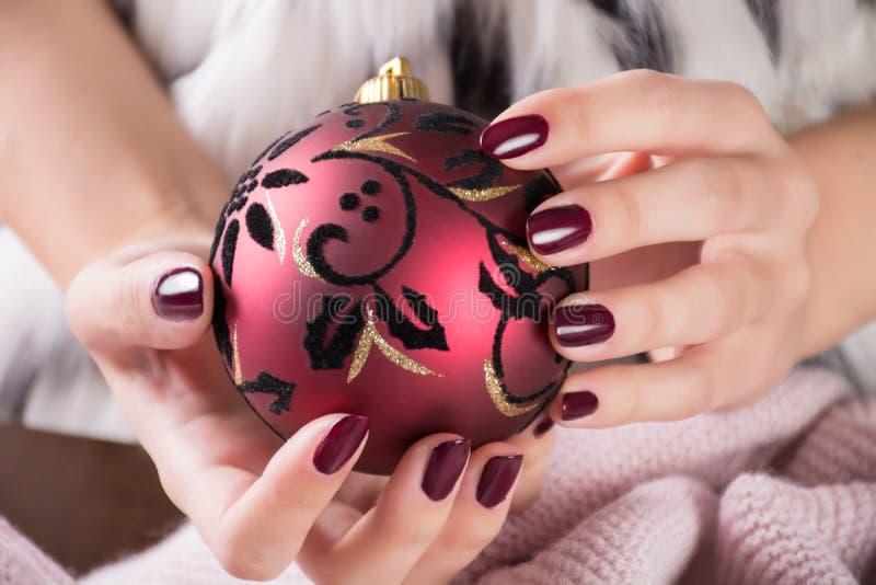 Ragazza con il gel e la tenuta della lucidatura di unghie di colore del vino rosso della palla di Natale fotografia stock