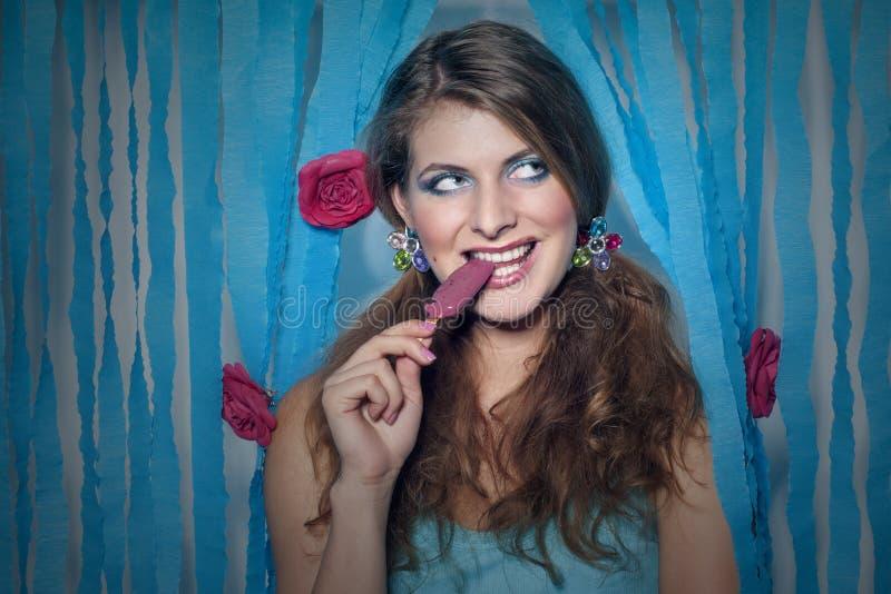 Ragazza con il ghiacciolo ed i fiori in suoi capelli fotografia stock