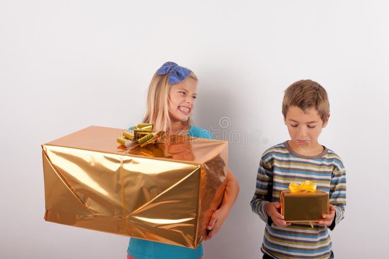 Ragazza con il grande contenitore di regalo che gongola sopra suo fratello e la sua s immagini stock libere da diritti
