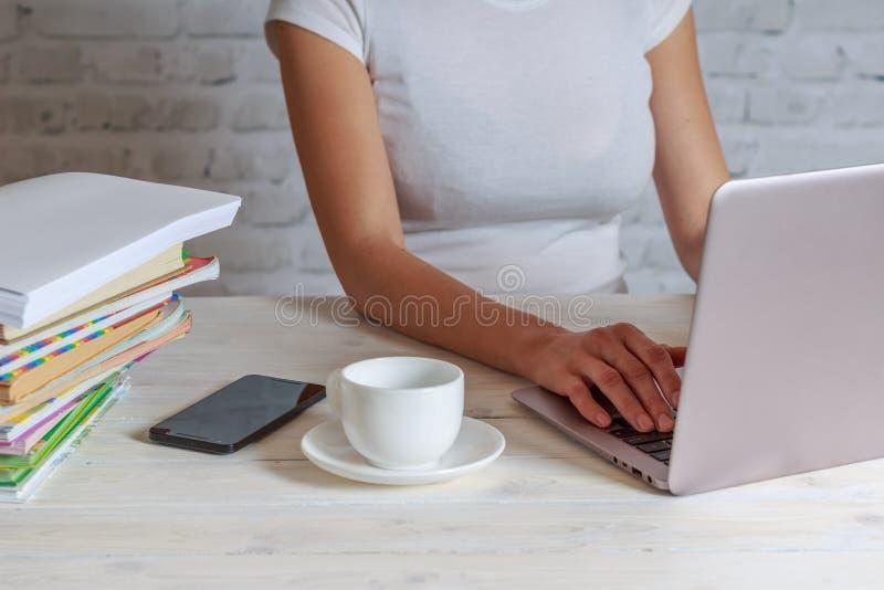Ragazza con il lavoro della tazza di caffè a casa sul computer immagine stock