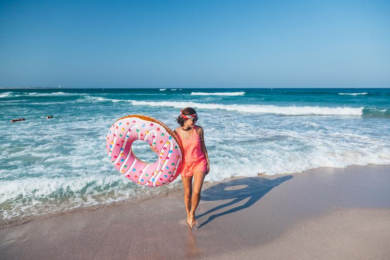 Ragazza con il lilo della ciambella sulla spiaggia immagine stock libera da diritti