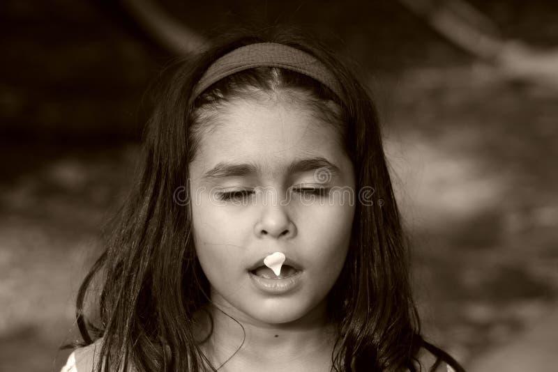 Ragazza con il petalo del fiore sulla bocca fotografie stock