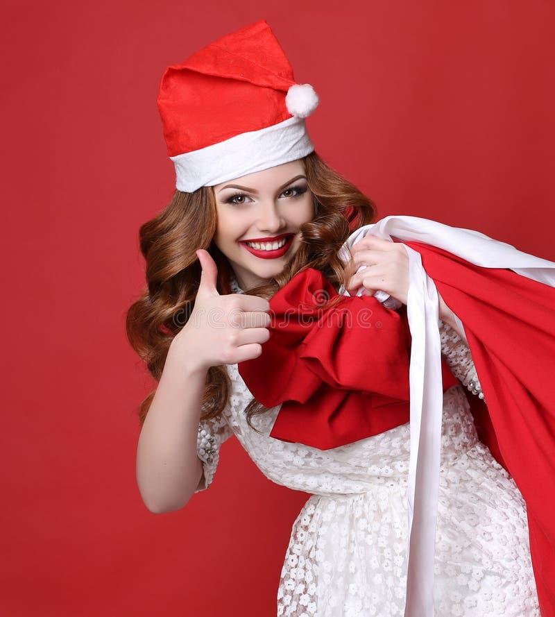 Ragazza con il sorriso affascinante, in cappello di Santa, con la grande borsa con immagine stock libera da diritti