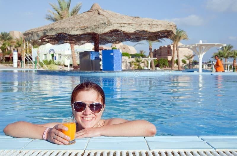 Ragazza con il succo di arancia all'hotel di ricorso immagine stock