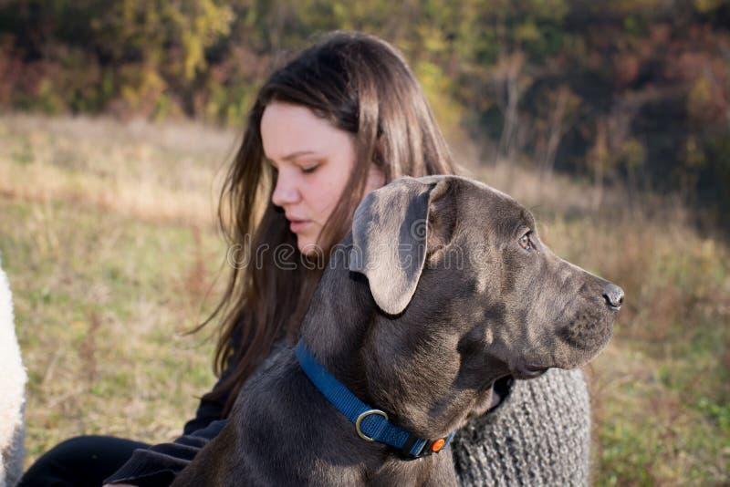 Ragazza con il suo cucciolo di corso della canna fotografia stock
