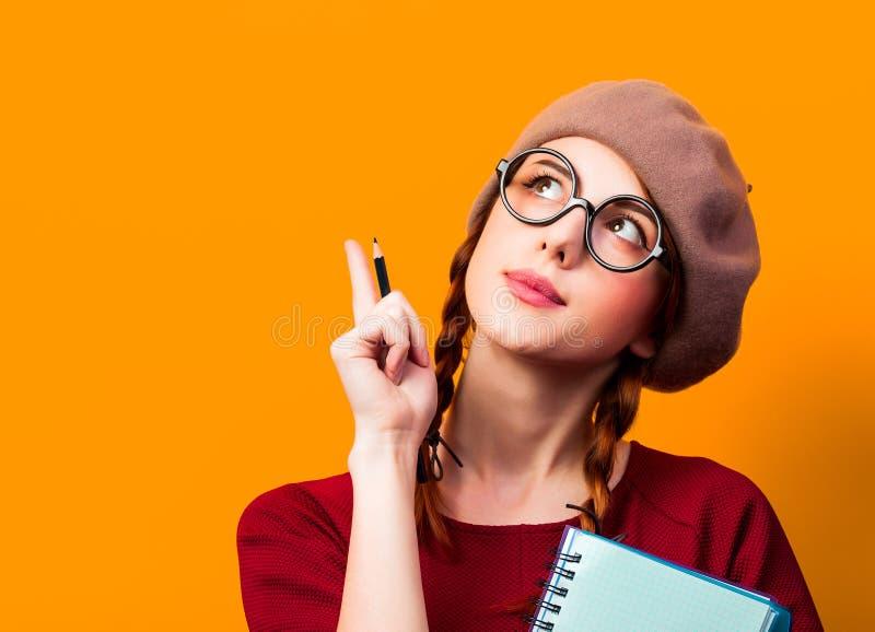 Ragazza con il taccuino e la matita su fondo giallo immagini stock