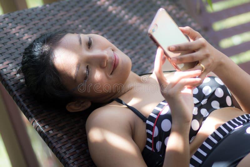 Ragazza con il telefono che si trova sul letto di campo immagine stock libera da diritti