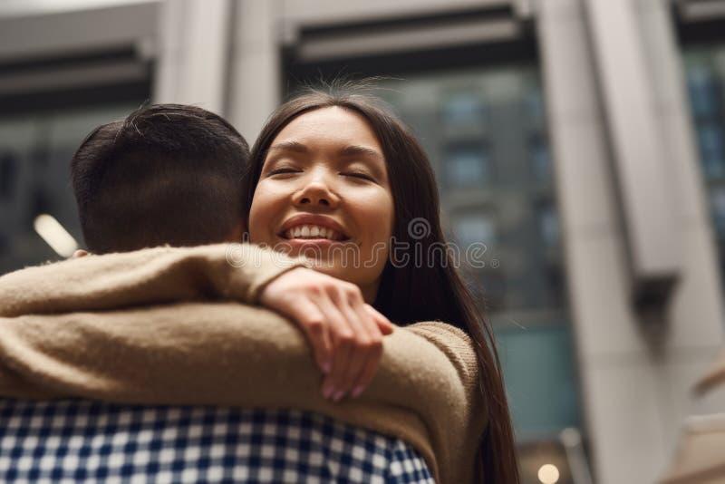 Ragazza con il tipo romanticamente che abbraccia sul fondo della costruzione fotografia stock