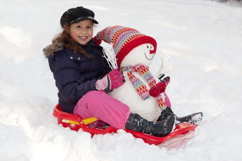 Ragazza con il toboggan e pupazzo di neve fotografia stock libera da diritti