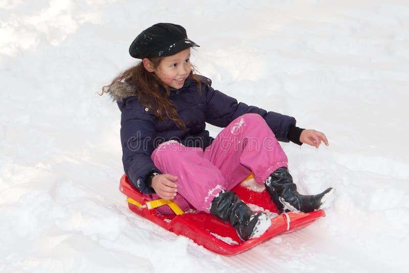 Ragazza con il toboggan nella neve fotografie stock