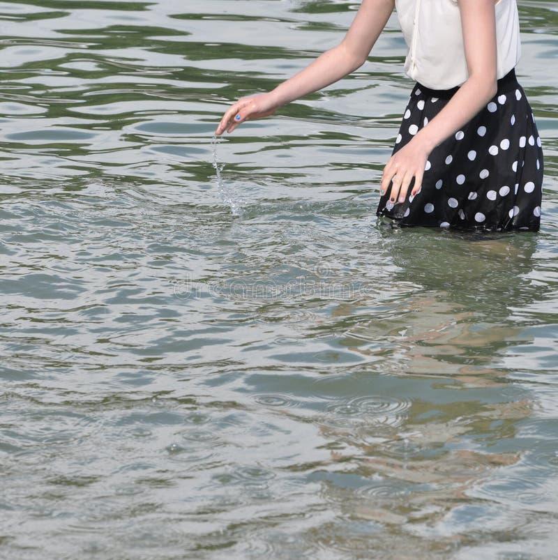 Ragazza con il vestito punteggiato che spruzza acqua immagini stock