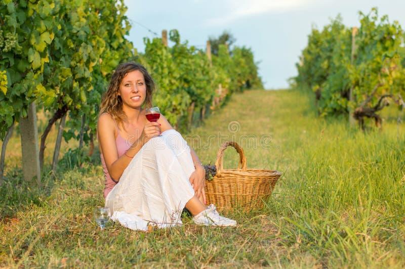 Ragazza con il vetro di vino che si siede nella vigna immagini stock