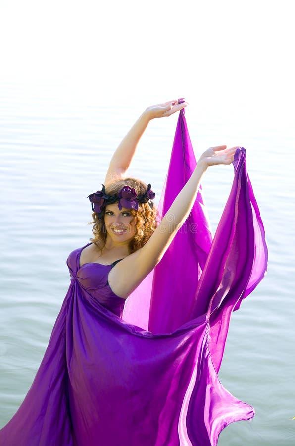 Ragazza con il volo dei capelli ricci nel vestito viola immagini stock libere da diritti