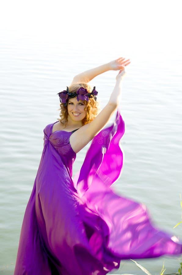 Ragazza con il volo dei capelli ricci nel vestito viola immagine stock
