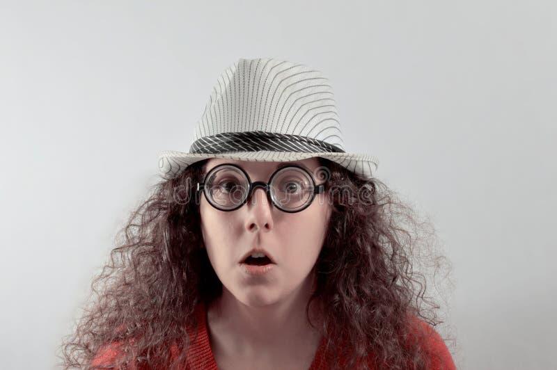 Ragazza con l'espressione ridicola, il cappello ed i vetri immagini stock