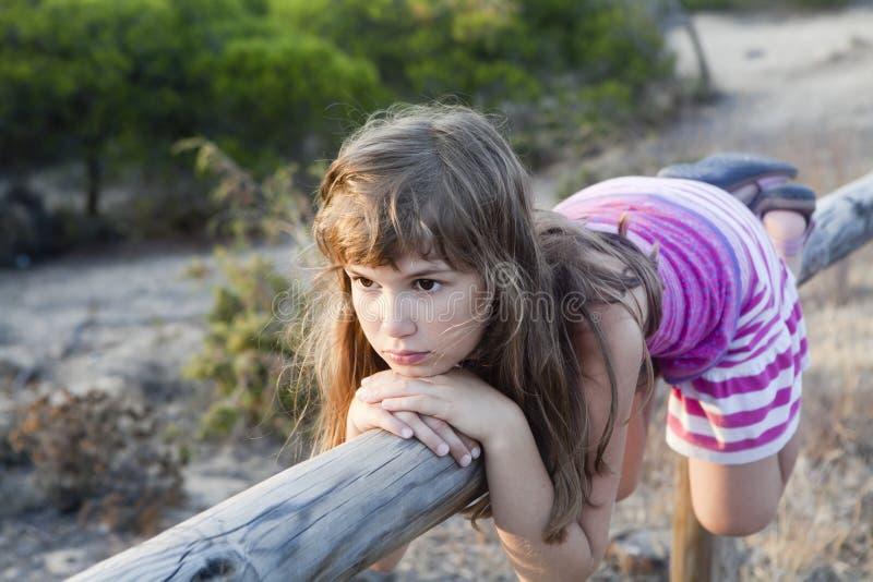 Ragazza con l'inclinzione sulla rete fissa di legno fotografia stock libera da diritti