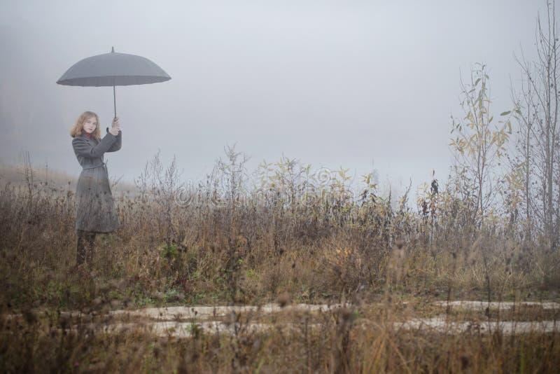 Ragazza con l'ombrello nel campo di autunno fotografie stock