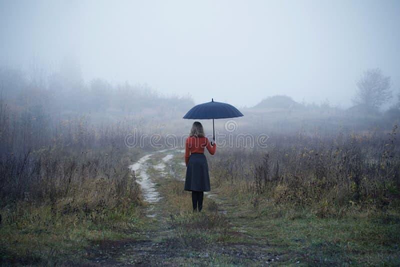 Ragazza con l'ombrello nel campo di autunno immagine stock