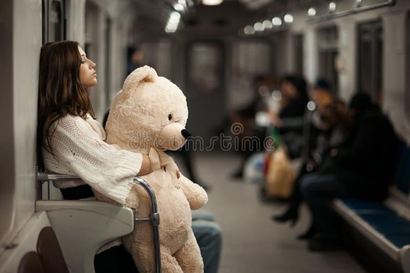 Ragazza con l'orso in un'automobile di sottopassaggio immagine stock