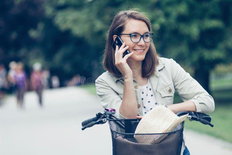 Ragazza con la bicicletta facendo uso dello smartphone immagini stock libere da diritti