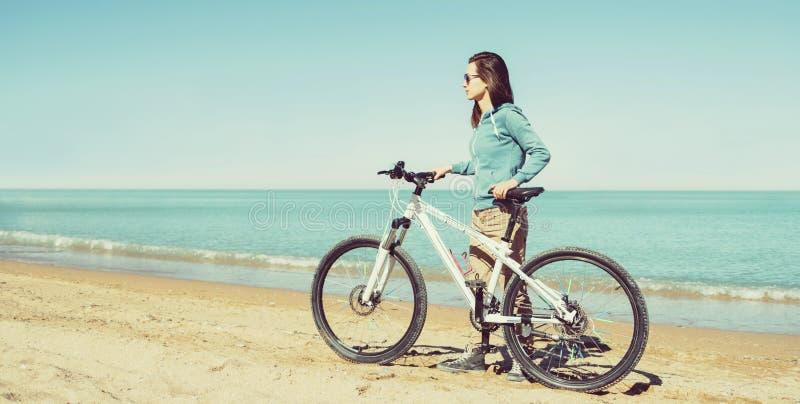 Ragazza con la bicicletta sulla spiaggia immagine stock