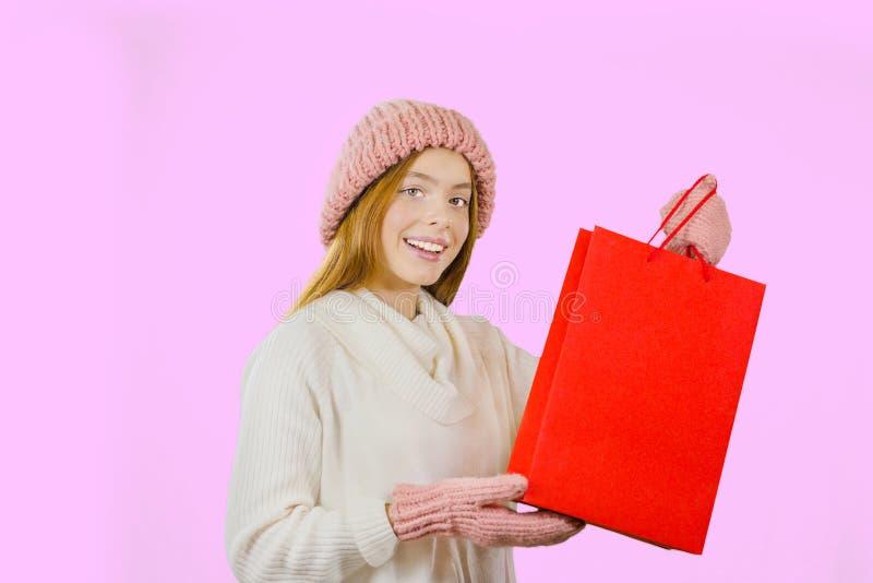 Ragazza con la borsa rossa del regalo in mani su un fondo isolato immagini stock
