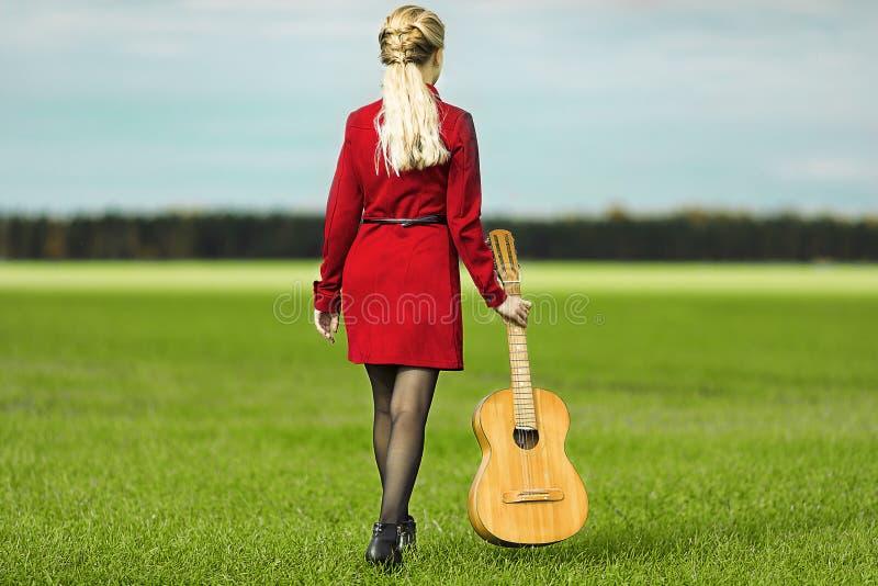 Ragazza con la chitarra in vestito rosso che cammina sul campo verde immagine stock