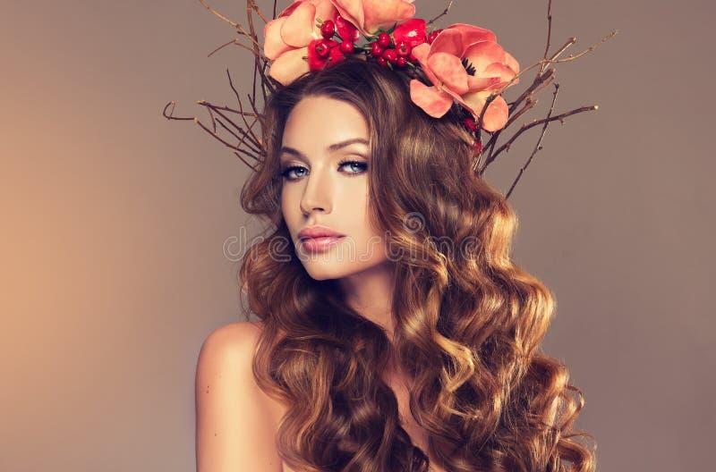 Ragazza con la corona delicata dai fiori, dai frutti e dai ramoscelli su lei capa fotografia stock