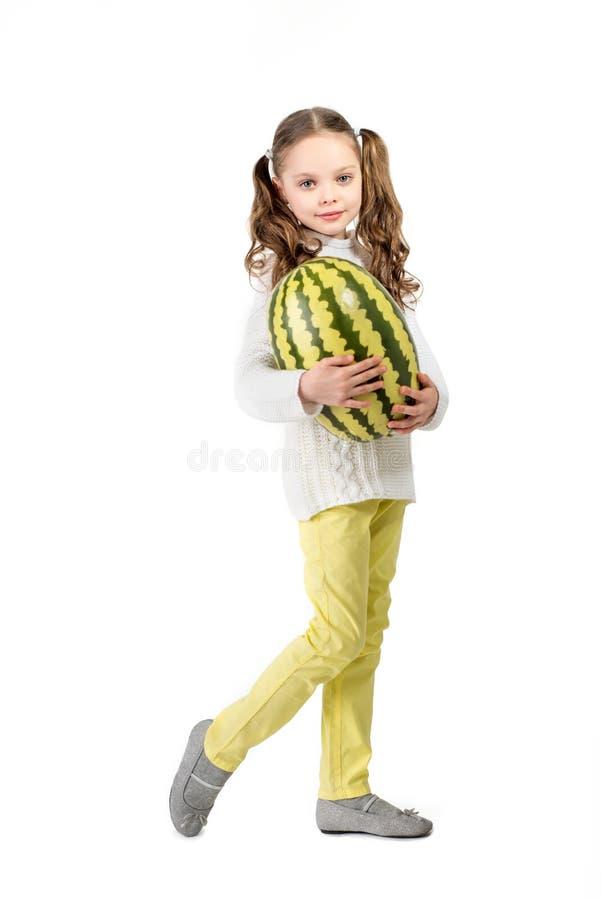 Ragazza con la grande anguria del giocattolo su un fondo bianco immagini stock libere da diritti