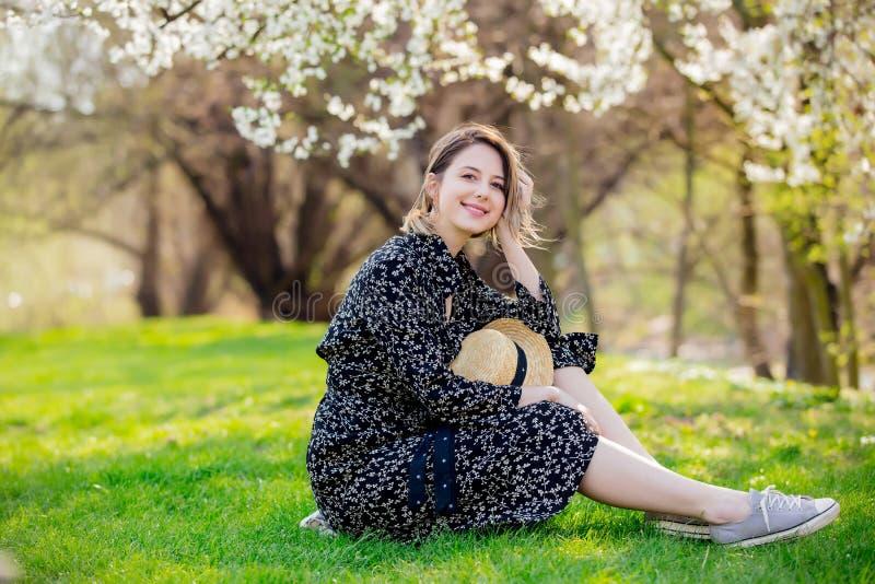 Ragazza con la macchina fotografica che si siede vicino ad un albero di fioritura i fotografia stock libera da diritti