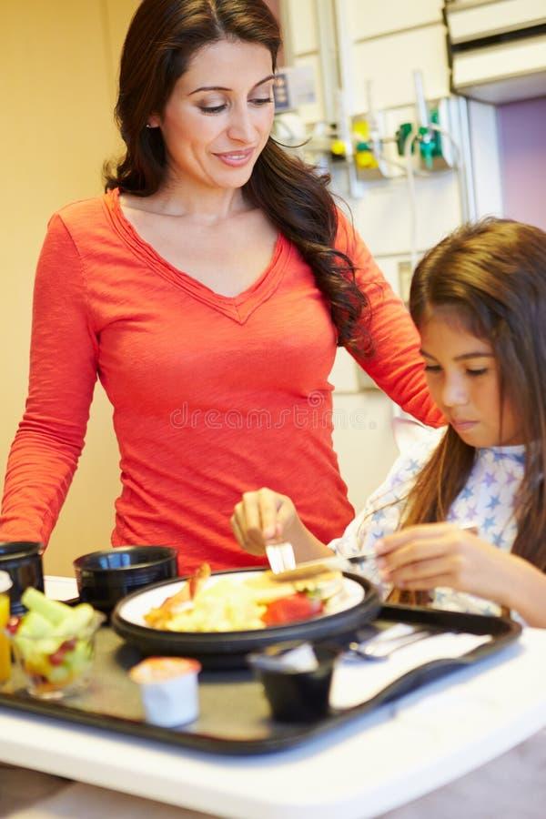 Ragazza con la madre che mangia pranzo nel letto di ospedale fotografia stock