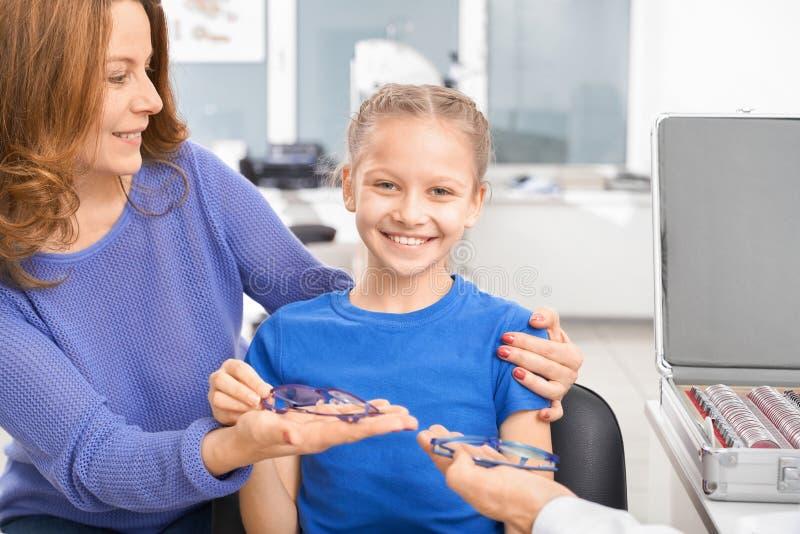 Ragazza con la madre che sceglie i vetri nella clinica di oftalmologia fotografia stock libera da diritti