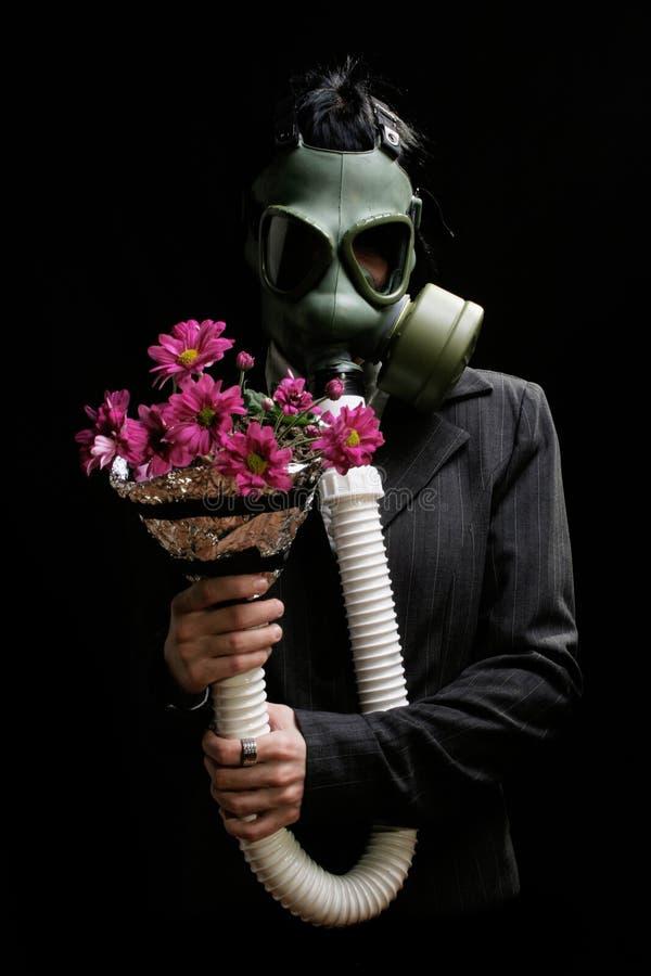 Ragazza con la maschera antigas ed i fiori fotografia stock libera da diritti