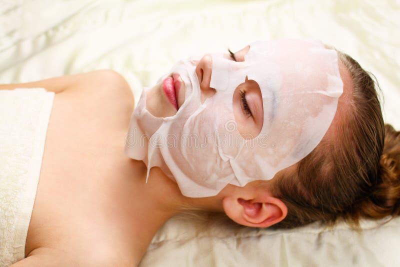 Ragazza con la maschera del panno per il fronte immagine stock