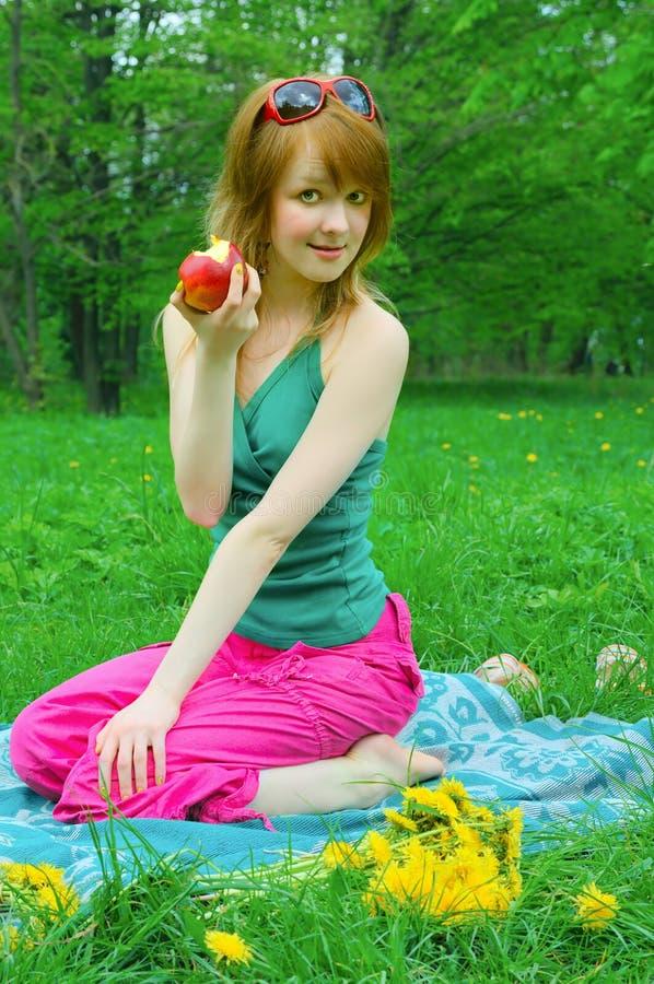 Ragazza con la mela sul coverlet fotografia stock libera da diritti