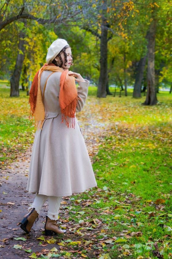 Ragazza con la a nel suoi cappotto e presa su una passeggiata in autunno fotografia stock