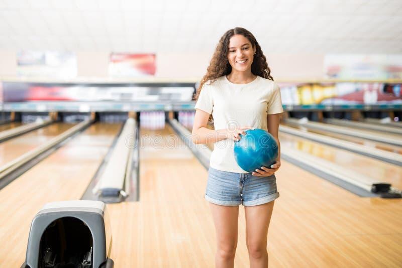 Ragazza con la palla che gioca in vicolo di bowling al club immagine stock libera da diritti