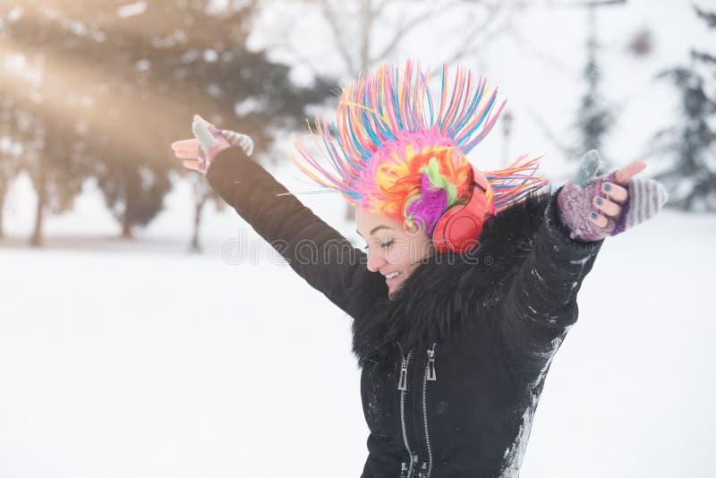 Ragazza con la parrucca variopinta del pagliaccio e cuffie il giorno della neve fotografia stock libera da diritti