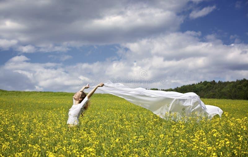 Ragazza con la parte del panno bianca in vento fotografia stock libera da diritti
