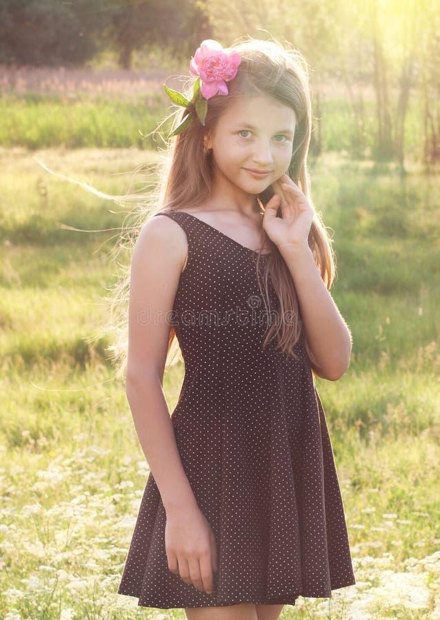 Ragazza con la peonia in suoi capelli che esaminano la macchina fotografica immagine stock libera da diritti