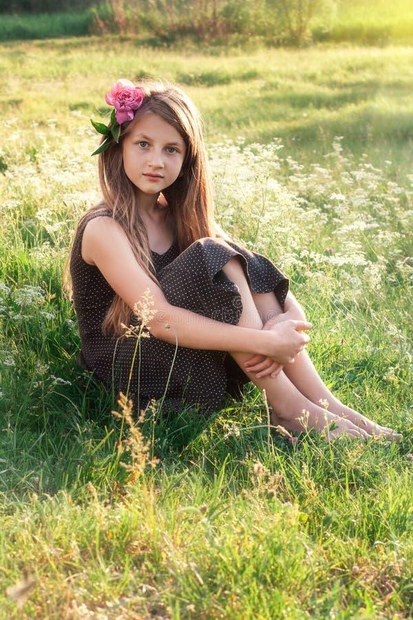 Ragazza con la peonia in suoi capelli che si siedono sul campo e che esaminano fotografia stock libera da diritti
