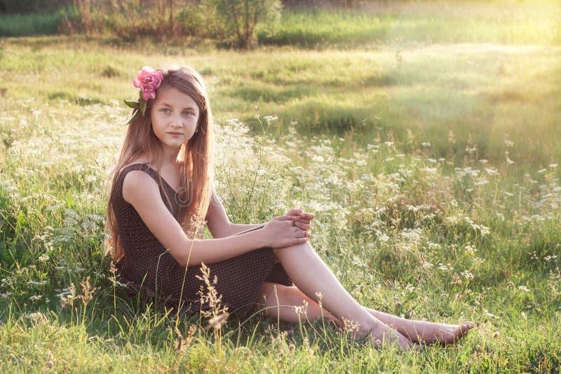 Ragazza con la peonia in suoi capelli che si siedono sul campo e che guardano int immagine stock