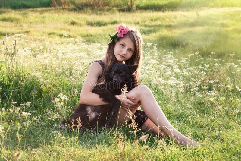 Ragazza con la peonia in suoi peli che segnano cane nero fotografia stock